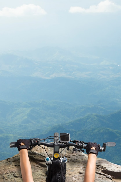 マウンテンバイク、マウンテンビューの上に見下ろして立っている自転車ハンドルに乗っている女性 Premium写真