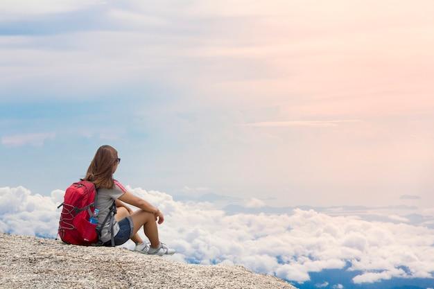 バックパックを持つ女性は日没で夏の山の霧に座る Premium写真