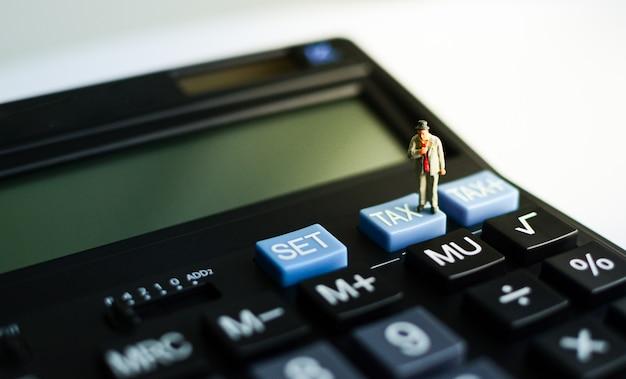 Миниатюрный бизнесмен стоя на голубой кнопке «налога» черного калькулятора с световым эффектом на правильной верхней стороне используя как концепция возврата налога, финансов и дела. Premium Фотографии