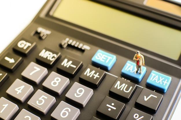 Миниатюрный бизнесмен стоя на голубой кнопке «налога» черного калькулятора с световым эффектом на левой верхней стороне используя как концепция возврата налога, финансов и дела. Premium Фотографии