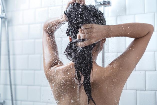 アジアの女性が入浴し、彼女は入浴して髪を洗っていた Premium写真