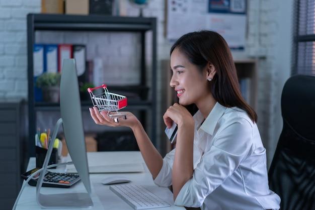 働く女性がオンラインで買うクレジットカードで彼女は買い物カゴを運んでいた Premium写真