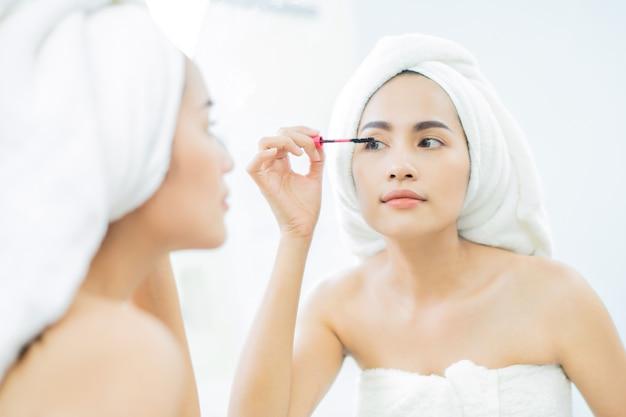 入浴後に黒のマスカラーまつげを適用するアジアの美しい女性 Premium写真