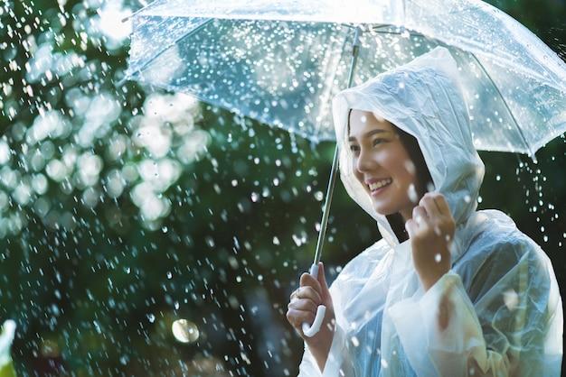 雨の日のアジアの女性が屋外のレインコートを着て Premium写真