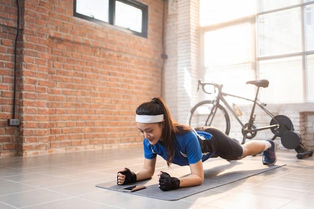 Велосипедист тренируется с позой на доске в доме. она использует таймер Premium Фотографии