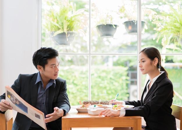 アジアのビジネスマンは、レストランで昼食を取るために休憩中です。新聞を読んでいる男性のレストラン。 Premium写真