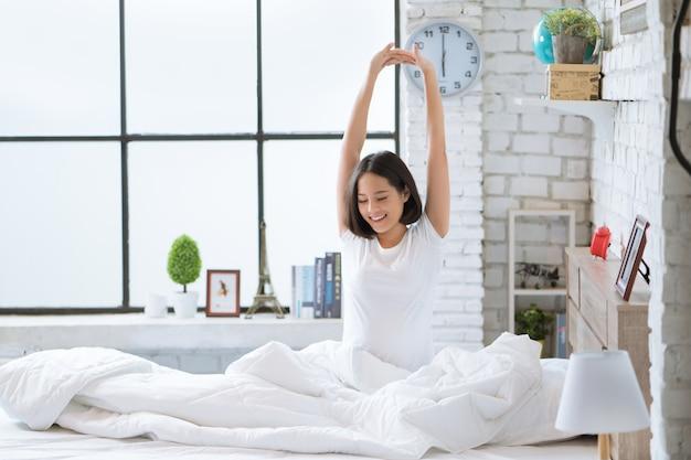 Азиатские женщины она лежит в постели и просыпается утром. она чувствовала себя очень освеженной. Premium Фотографии