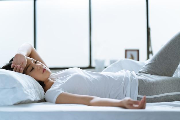 アジアの女の子はベッドの頭痛です。 Premium写真