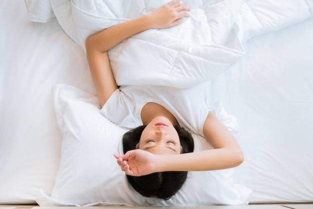 アジアの女の子はベッドで頭が痛む。トップビュー Premium写真