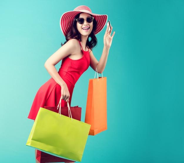 女性は買い物をしています夏には彼女はクレジットカードを使用していて買い物を楽しんでいます。 Premium写真