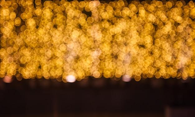 きらびやかな輝くと輝くデフォーカスゴールドライト照明屋外の背景 Premium写真