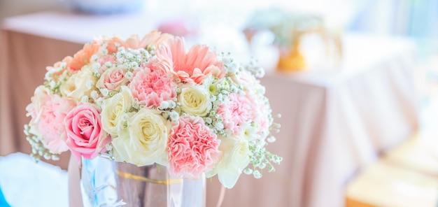 レセプションテーブルの背景に咲く新鮮な花の花束 Premium写真