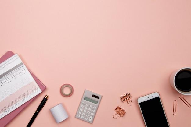 Офисный стол со смартфоном и другими канцелярскими принадлежностями на розовом фоне. Premium Фотографии