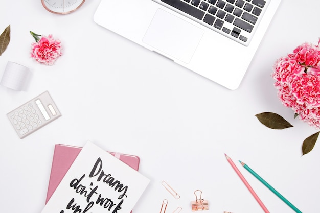 Женщина рабочее место с ноутбуком, ноутбук, розовый цветок гвоздики, смартфон Premium Фотографии