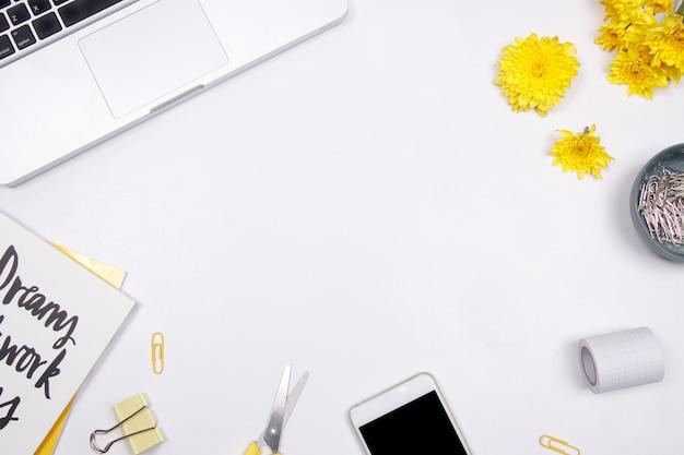 Женщина рабочее место с ноутбуком, желтый цветок и смартфон на белом фоне Premium Фотографии