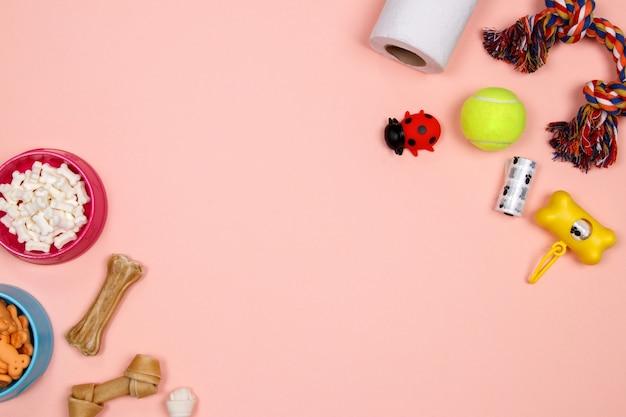 Аксессуары для собак, продукты питания и игрушки на розовом фоне. квартира лежала. вид сверху. Premium Фотографии