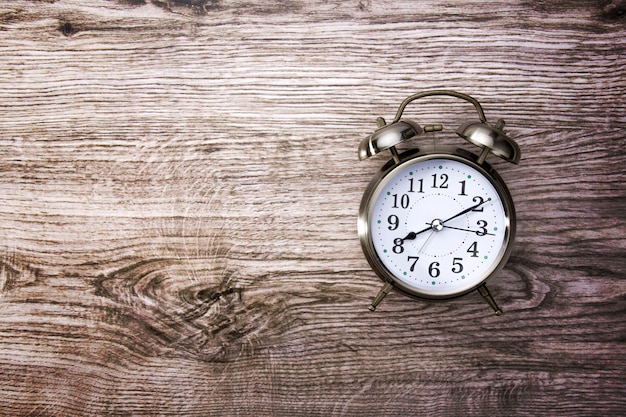 木製のテーブルにレトロな目覚まし時計とビンテージ背景 Premium写真