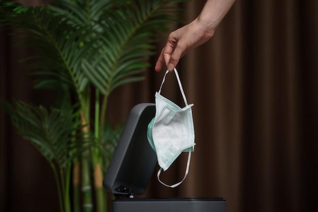 使用済みの汚れたサージカルマスクをゴミ箱に置く手。マスクはゴミやほこりやコロナウイルスを保護します。 Premium写真