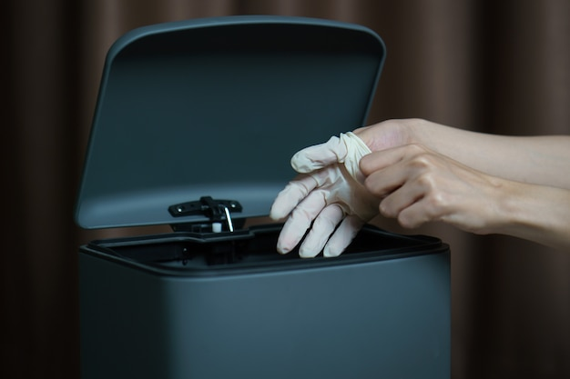 使用済みの汚れた手術用手袋をゴミ箱に置く手。マスクはゴミやほこりやコロナウイルスを保護します。 Premium写真