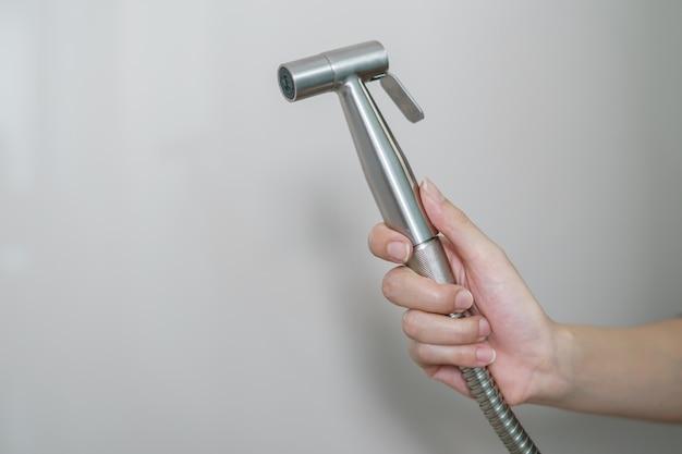 Рука женщины используя душ биде хрома сидя на туалете. Premium Фотографии
