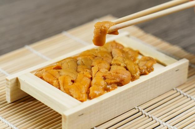 お箸でうに寿司。ウニ、日本料理。 Premium写真