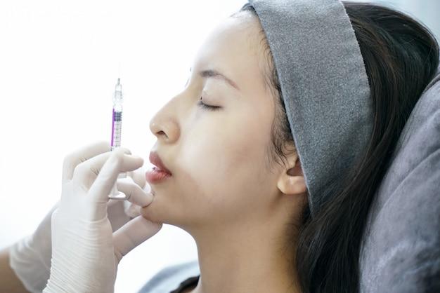 ビューティークリニック注射における若返り手続き彼女のあごに女性の注射。 Premium写真