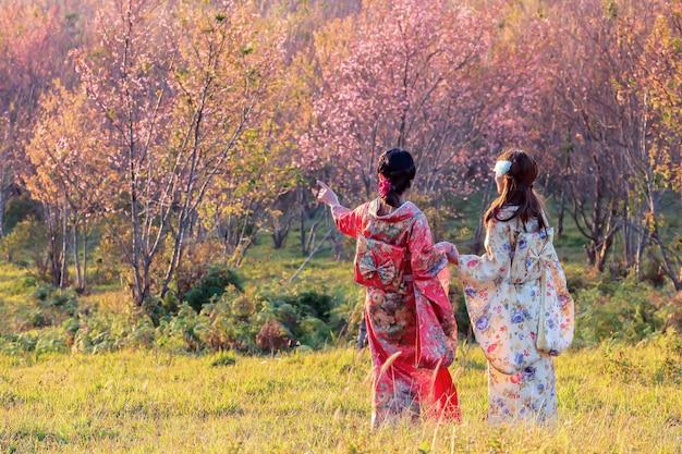 Азиатская женщина нося японское традиционное кимоно на саде сакуры. Premium Фотографии
