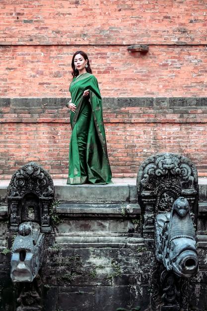 Красивые женщины в платье сари стоя позируют священному колодцу в королевском дворце на площади патана дурбара. Premium Фотографии
