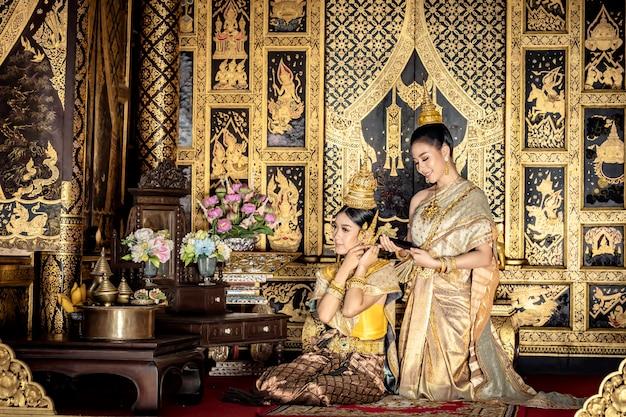 美しいタイの女性は、伝統的なタイの民族衣装を着ています。 Premium写真