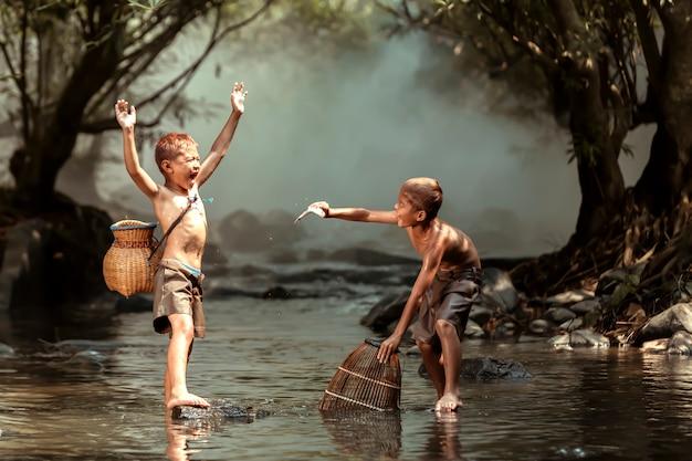 Два мальчика ловят рыбу в ручье возле дома в сельской местности таиланда Premium Фотографии