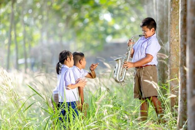Мальчик играет на саксофоне развлекайся, слушая друзей. Premium Фотографии