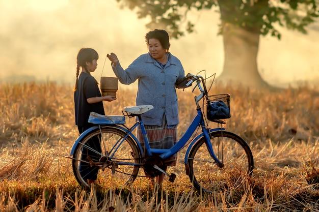 Бабушка собирается забрать свою племянницу. езда на велосипеде в храм, чтобы сделать заслуги в соответствии с буддийскими традициями. Premium Фотографии