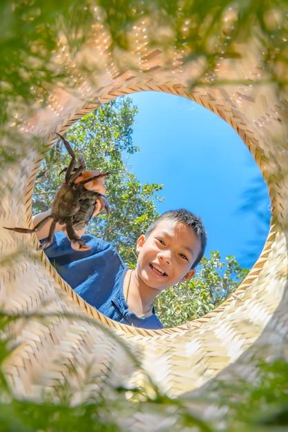 タイの農家の少年は用心棒でカニを喜んでキャッチ Premium写真