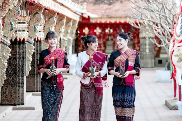 Три тайские девушки в племени фу тай, стоящие в районе тайского храма Premium Фотографии