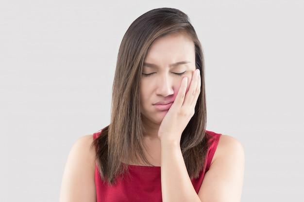 歯痛で苦しんでいる、アジアの女性が苦しんでいる赤いシャツを着て Premium写真