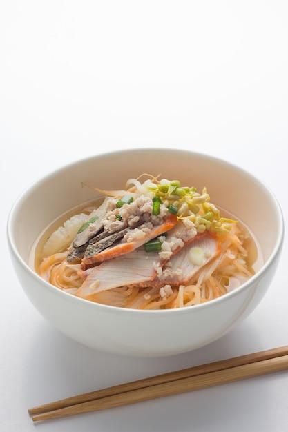 チキン、ボウルに野菜、素朴な木製のアジアンヌードル。 Premium写真