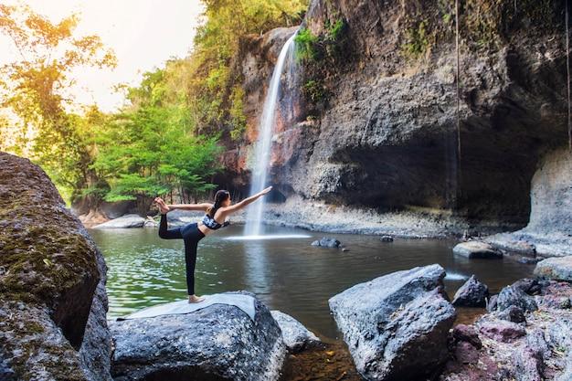 Молодая девушка занимается йогой возле водопада Premium Фотографии