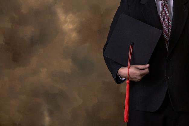 ビジネスの男性は卒業の帽子を保持しています。 Premium写真