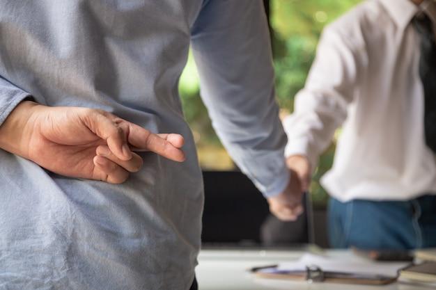 握手しているビジネスマンと指を握っているビジネスマンの一人が後ろで交差し、裏切りを表します。 Premium写真
