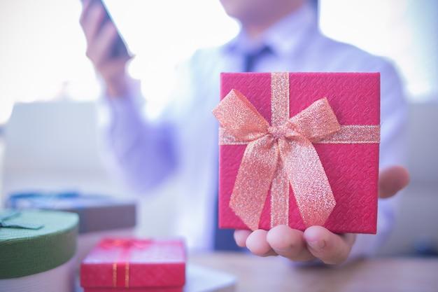 Служба доставки в офис. обрезанное выстрел деловой человек в рубашке, сидел на столе с красной подарочной коробке. Premium Фотографии