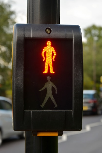 押しボタンは横断歩道で照らされた明るいストップ男と信号交通信号制御を待つ Premium写真