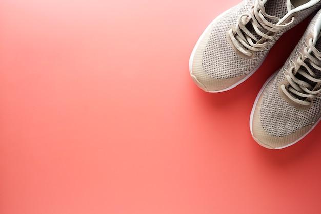 ピンクの背景にスポーツシューズのフラットレイアウト Premium写真