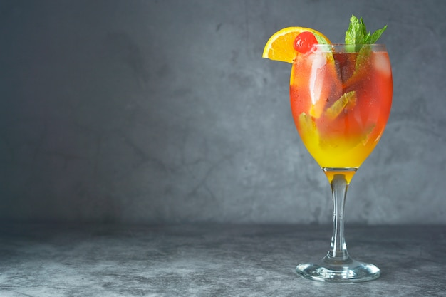 Летний коктейль. апельсиновый сок с мятой, сиропом, кусочками фруктов и вишней со льдом. Premium Фотографии