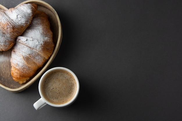 Кофе с круассаном в деревянной коробке в форме сердца. копировать пространство Premium Фотографии