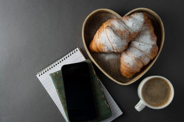木製のハート形のボックスでクロワッサンとコーヒー。スペースをコピーします。 Premium写真