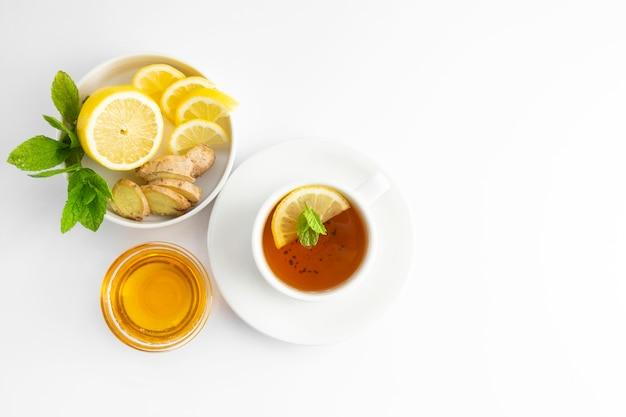 白い背景の上に蜂蜜とレモンの新鮮なお茶 Premium写真