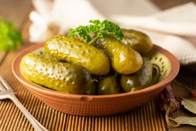 きゅうりのマリネ木製のテーブルのボウルに野菜をピクルスします。 Premium写真