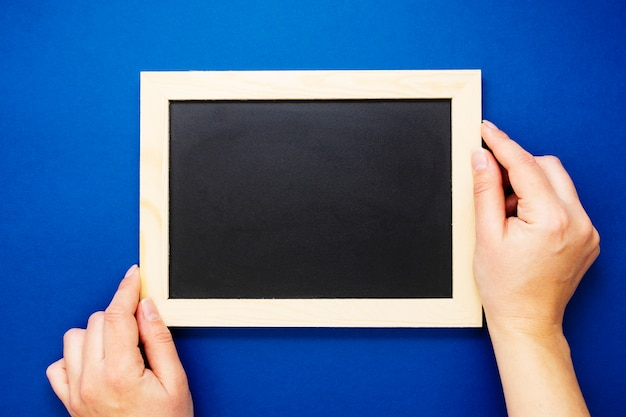 黒板のモックアップ。分離された青色の背景に黒板を保持している女性の手。コピースペース、フラットレイアウト。ビジネス、教育の概念。 Premium写真