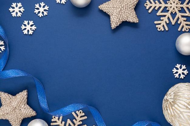 ブルー抽象的なクリスマスミニマルなスタイルの背景に銀の雪、つまらないもの、青いリボン。テキスト用のスペースと青のモックアップ。 Premium写真