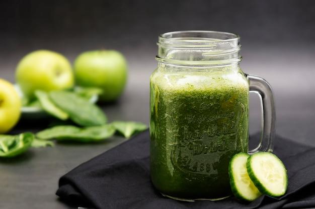 石工の瓶マグ暗い食べ物写真で健康的な緑のスムージー。健康食品のコンセプト。 Premium写真